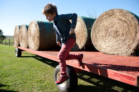 Boy jumping off the side of a farm tractor trailer with bales of hay.
