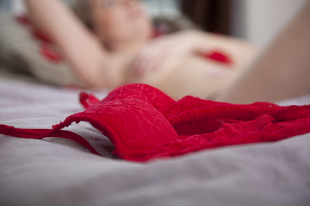 woman blurry in the background with red lacy lingerie bra in the foreground of a boudoir bedroom shoot