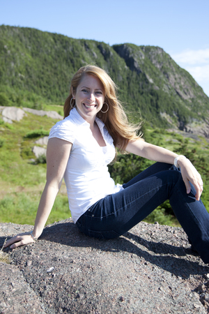 owning: a woman traveling the east coast with smile on her face in the sun Stock Photo