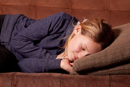 Female teenager sleeping on a sofa or couch.