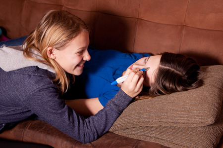 pesky little sister writes on sister's forehead while asleep or sick