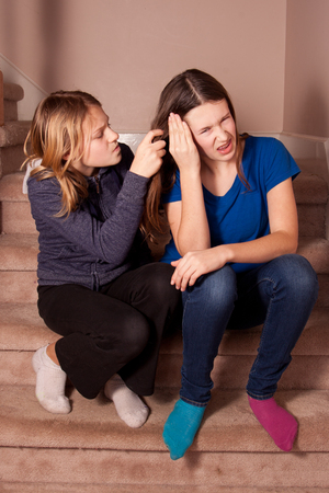harass: Sisters sat on the stairs at home with one pulling the others hair. Stock Photo