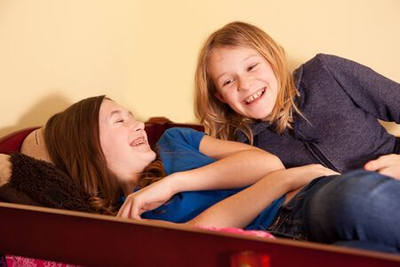 Two teen girls giggling together in a bunk bed.