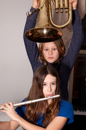 Two young girls fooling around with musical instruments.
