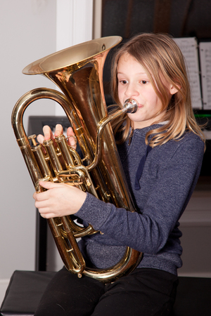 Young girl blowing on a baritone horn.