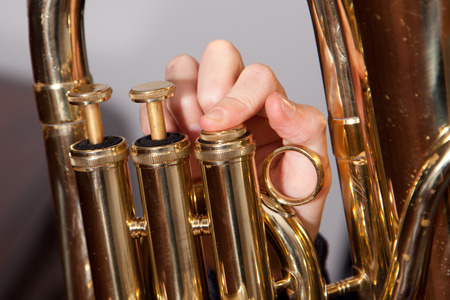 Fingers on euphonium valves of a horn. Stock Photo