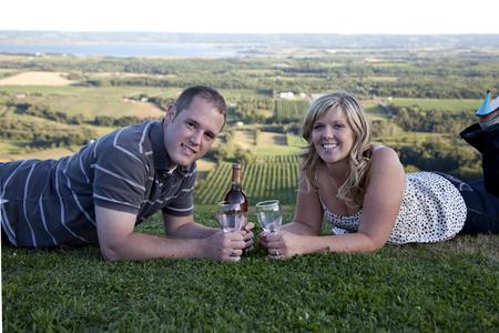 bebes lindos: hermosa joven pareja yacía sobre hierba vasos de vino celebran su romance Foto de archivo
