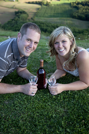 young couple on mountain top with wine