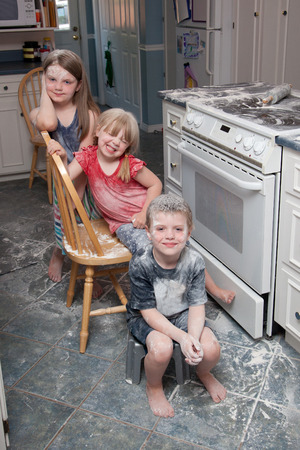 Three naughty children who have just made a mess in the kitchen sit beside the oven looking happy