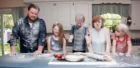 an angry family in the kitchen after a food fight and baking an apple pie. Stock Photo - 82914017