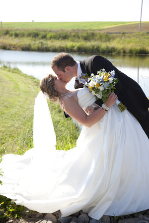 a bride and groom dance and dip in a long kiss Stock Photo