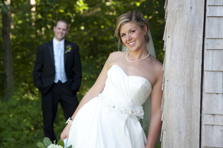 Beautiful bride poses for portrait with husband in the background
