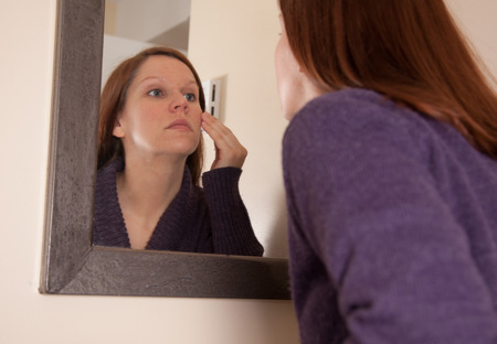 a young woman touches and examines her face and skin in her bathroom mirror Stock Photo
