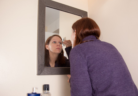 young woman in purple sweater looks in bathroom mirror and uses wand to put on eyebrow powder or makeup at home Stock Photo