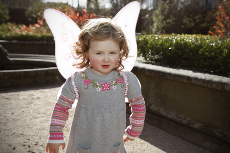 pretending: small child with curly hair backlit by the sun, wearing pink butterfly wings