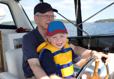 grandfather holding his small grandchild, teaching him to drive a boat Stock fotó