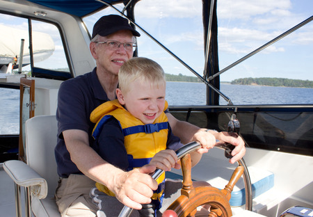 a senior man holds his grandson, wearing a life vest, as they steer a boat from the helm