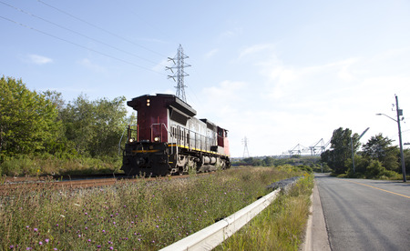 a red and black train comes along tracks in grass and blue sky, container pier behind