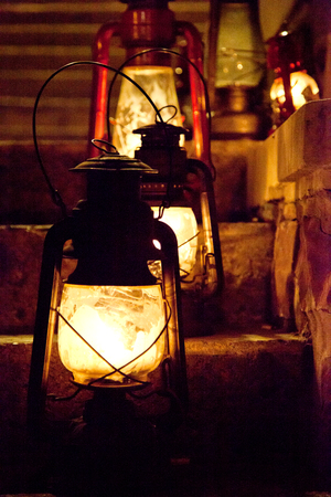 oil lamp: old fashioned oil lamps or lanterns sitting on a flight of stairs at night