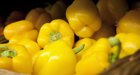 a group of bright yellow bell peppers at the market
