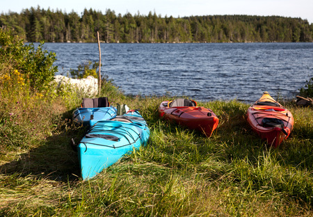 red, orange, blue kayaks in front of a lake on a hot summer day