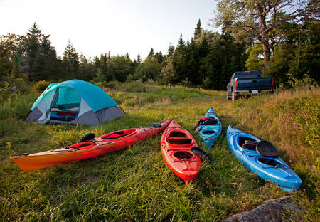 a wilderness campsite with a pickup truck, four colorful kayas, and a pitched tent in the woods