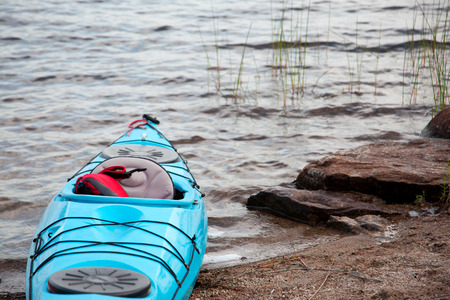 a turquoise kayak by the grass in a lake with copy space