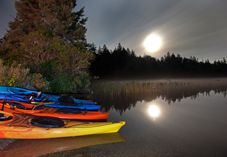 moonlight reflecting in a lake with kayaks by the shoreline Stock Photo