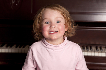 a cute curly red haired child gives a big toothy grin at home on the piano bench