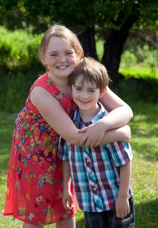 a freckled red haired girl hugs her brown haired brother, smiling outside in the sun