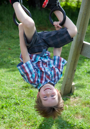a smiling brown haired boy grins as he hangs upside down on rings on a swing set outside
