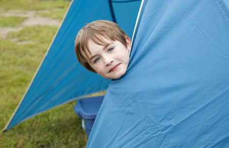 cute brown haired child plays hide and seek inside a blue tent while camping