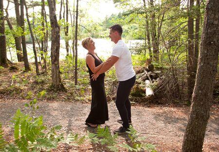 An einem Sommersee lacht eine blonde Frau mit ihrem gutaussehenden Ehemann Standard-Bild - 84501403