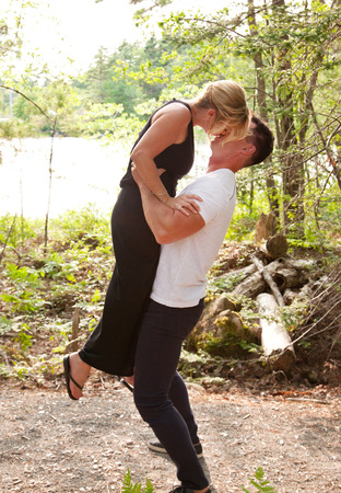a strong handsome man lifts a beautiful blond woman in the air while they kiss in the forest
