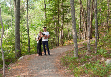 a couple with their pet dogs stand together on a winding forest road in summer