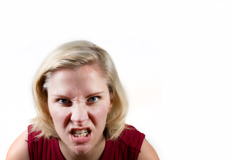 a woman makes an extremely angry or determined face in white studio background with copy space