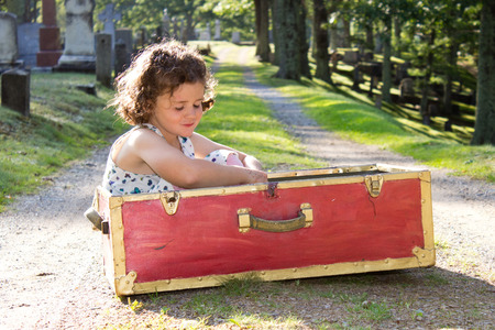 seperation: a small lonely girl in a red box in a cemetery  Stock Photo