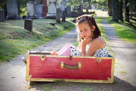 small child in a red box is sad in a graveyard