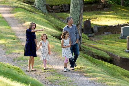 a father and mother walking in the woods with her young children, pointing and teaching about nature