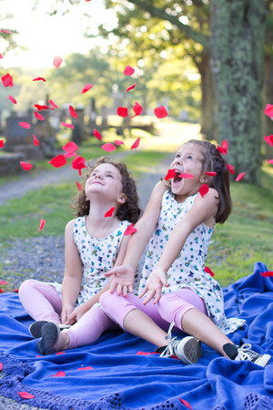 two little girls shriek or squeal with delight as flowers and thrown on them