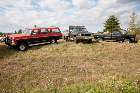 light duty: three old work trucks or vehicles parked in a field waiting for a job