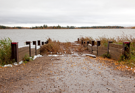 a canoe or boat ramp leading to a marshy swamp in autumn