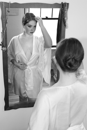 woman in a silk robe looks at herself in a mirror