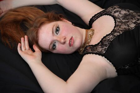 a freckled red haired woman lays on bed in black lace looking seductive