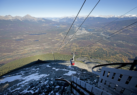 view from a mountain top down to the valley below with a red skytram taking tourists