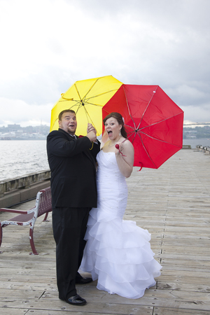 newlyweds with yellow and red umbrellas get blown away by a storm
