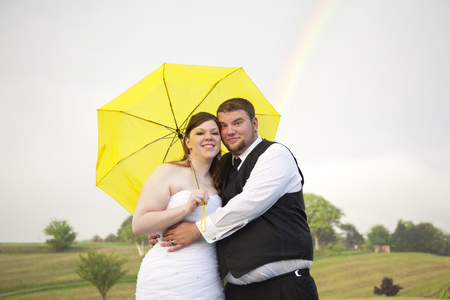 a rainbow behind a newly married couple on a cloudy day under an umbrella