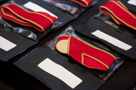gold medals with red ribbons lined up for presentation at ceremony Stock Photo
