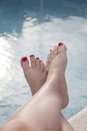 relaxing by the swimming pool, feet up with painted red toenails