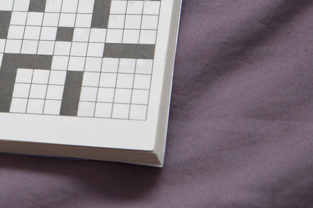 A crossword puzzle with empty spaces on a purple copy space Stock Photo